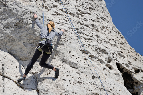 Poster Alpinisme A woman climbing the rocks.