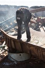 Worker Cutting The Metal In The Scrapyard