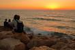 Zakochana para, chłopak i dziewczyna, przytuleni, siedzą na skalistym brzegu morza i podziwiają romantyczny zachód słońca