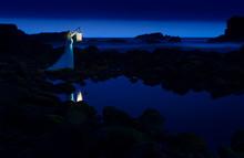 Dark Night, Blue Sea And Sky, Blonde Woman In Long Dress With Lantern