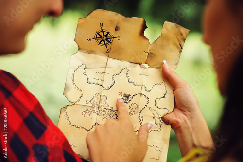 Fotografie, Obraz  Couple of lovers holding a pirate map in hands and looking for treasures