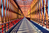Fototapeta Scene - Red iron bridge crossing a river with roadway.