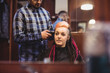 Woman getting her hair trimmed with trimmer