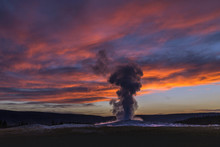 Old Faithful Geyser Eruption In Yellowstone National Park At Sunset, Wyoming, USA