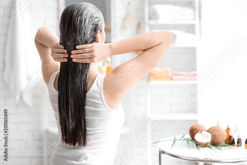 Fotografía  Young woman applying oil onto hair in bathroom