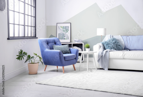 Valokuva  Stylish living room interior with comfortable sofa and armchair
