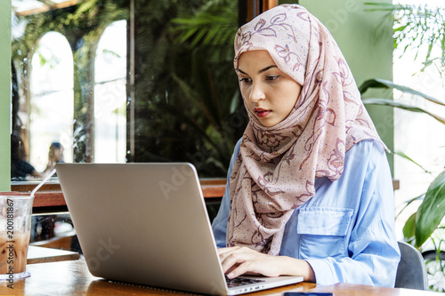 Fotomural  Islamic woman sitting and using laptop