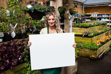 Smiling Female Florist Holding Blank Placard