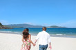 Back view of happy couple running on the beach. Concept of lifestyle.