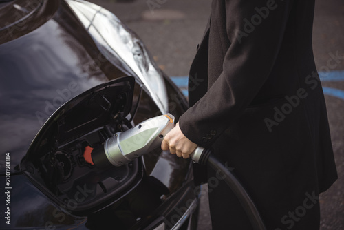 Man charging electric car at electric vehicle charging station