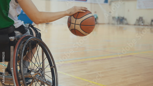 Wheelchair basketball player dribbling the ball quickly during training of disabled sportsmen