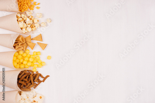 Valokuva  Golden colorful snacks - nachos, popcorn, croutons, chips in craft paper cone as border on white wood table with copy space