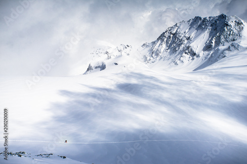 Photo sur Toile Taupe A lone skier exploring the snow fields and high mountains of the Swiss Alps