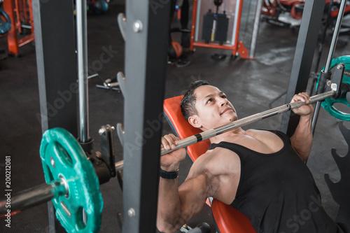Foto Muscular bodybuilder bench press workout with smith machine