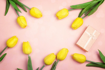 Pink background with yellow tulips and gift box. Flat lay, top view with copy space.