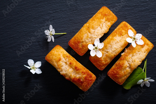 Fotografía Food concept mini French almond cake financier on black slate stone with copy sp