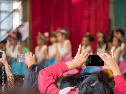 Canvas parent try to take video of their kid in acting day at school, by smartphone cam