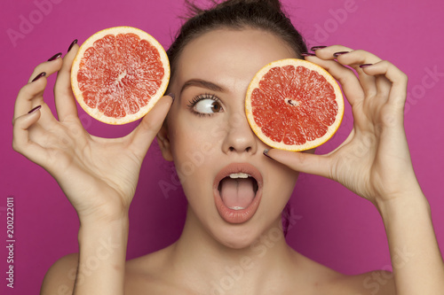 Young surprised woman posing with slices of red grapefruit on her face on pink background