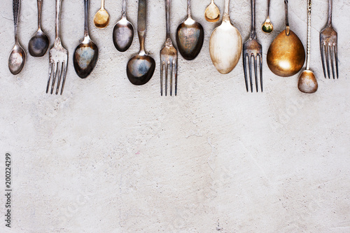 Background with vintage silverware on the grey table