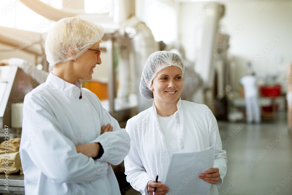 Fototapety, obrazy: Two young gorgeous female workers are having a chat while one of them holds papers with statistics.