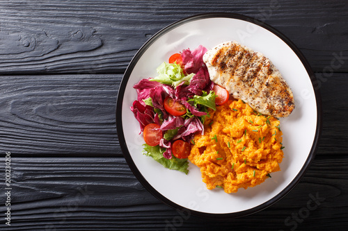 Foto  Delicious grilled chicken with garnish of sweet potato and fresh salad close-up on a plate