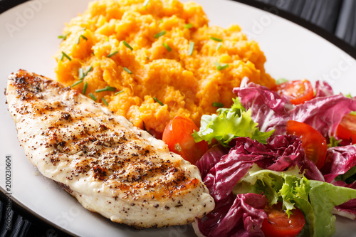 Grilled chicken fillet with mashed sweet potatoes and fresh lettuce close-up. horizontal