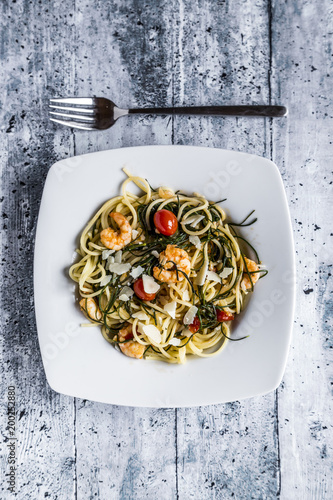 Tuinposter Hout Spaghetti with prawns, tomatoes and opposite-leaved saltwort