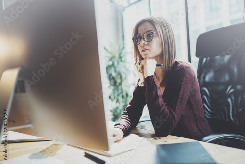 Attractive young businesswoman using desktop computer at modern working place at office.Blurred background.Horizontal.