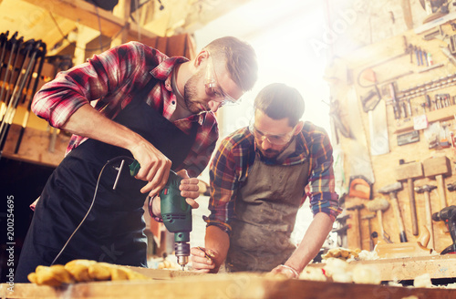 Fotografia  profession, carpentry, woodwork and people concept - two carpenters with electri