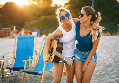 Papiers peints Statue Two young female friends hangout at the beach ,singing and relaxing in beautiful summer sunset.They hug each other.