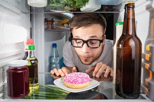 Mann betrachtet einen Donut im Kühlschrank