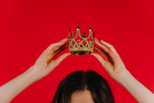 Golden Crown On A Red Background In Female Hands Over His Head, Woman Holds The Crown Over His Head - Copy Space