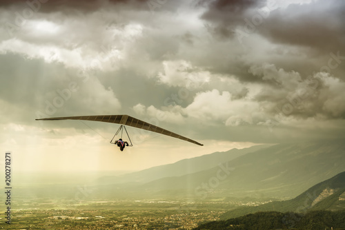 Dramatic shot of brave extreme hangglider pilot flying his wing in a stormy weather