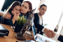 Bronze Statue Of Themis Stands On Table, Behind Which Sits Divorcing Parents With Little Girl.