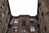 Facade of ruined old vintage red brick house with broken windows and grey overcast sky (location: Kamienico, part of former Jewish ghetto, Walicow street, Warsaw city, Poland) - 200288463