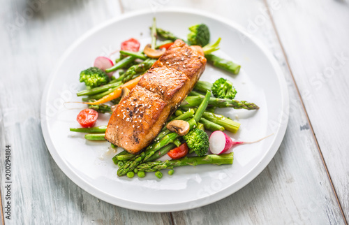 Tuinposter Kruidenierswinkel Roasted salmon steak with asparagos broccoli carrot tomatoes radish green beans and peas. Fish meal with fresh vegetable