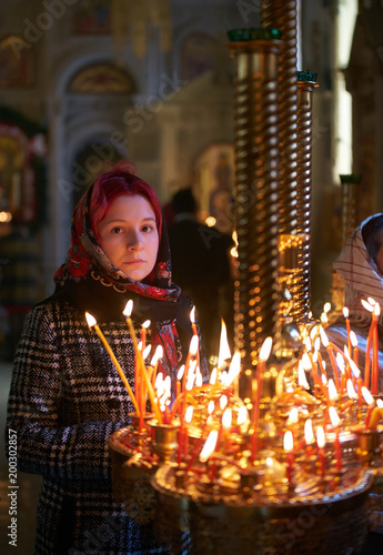 Praying young woman with candle near pedestal with many other