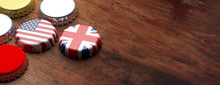 Beer Caps With UK And USA Flags On Wooden Background, Copy Space, Banner. 3d Illustration