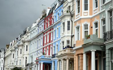 Pastellfarbene Häuserzeile in Notting Hill vor gewitterschwangerem Himmel
