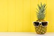 canvas print picture - Hipster pineapple with trendy sunglasses against yellow wood background. Minimal summer concept.