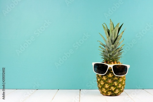 Hipster pineapple with trendy sunglasses against turquoise background. Minimal summer concept.