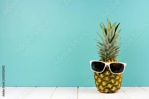 Hipster ananas z modnymi okularami przeciwsłonecznymi na turkusowym tle. Minimalna koncepcja lato.