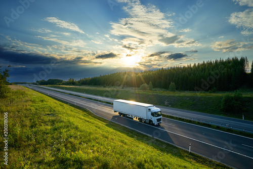 Fotografie, Obraz  White truck driving on the highway in the countryside in the rays of the sunset