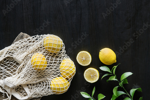 Tuinposter Fietsen Fresh yellow lemons on black background