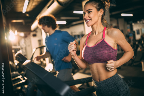 Spoed Foto op Canvas Fitness Horizontal photo of attractive woman jogging on treadmill at health club.