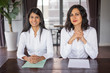 Two positive female workers sitting at desk in modern office. They are looking at camera. Female employees concept. Front view.