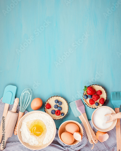 Keuken foto achterwand Koken Baking utensils and cooking ingredients for tarts, cookies, dough and pastry. Flat lay with eggs, flour, sugar, berries.Top view, mockup for recipe, culinary classes, cooking blog.