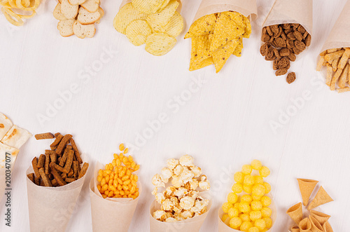 Fotografie, Obraz Summer fun fast food - different crunchy snacks in craft paper cornet as decoration border  on soft white wood board