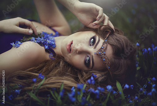 Fotografie, Obraz  Elf girl with long hair and blue eyes in the tiara rests in spring forest blue forest flowers