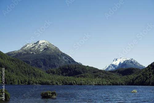 Foto auf Gartenposter Reflexion Paisaje de picos de montañas nevados y verdes con cielo azul frente a un lago en Nueva Zelanda